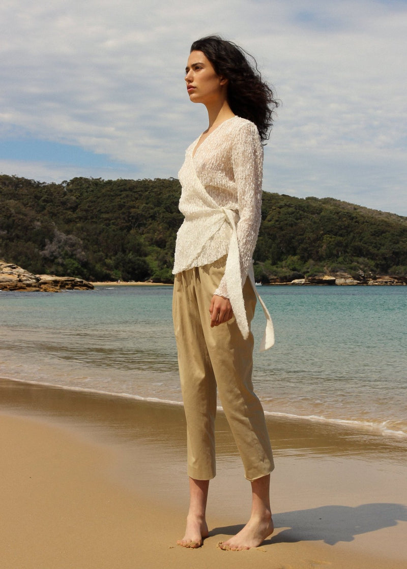 India on the beach wearing the Luela Fil Coupé-Plissé Wrap Top in Vanilla by Laundromat