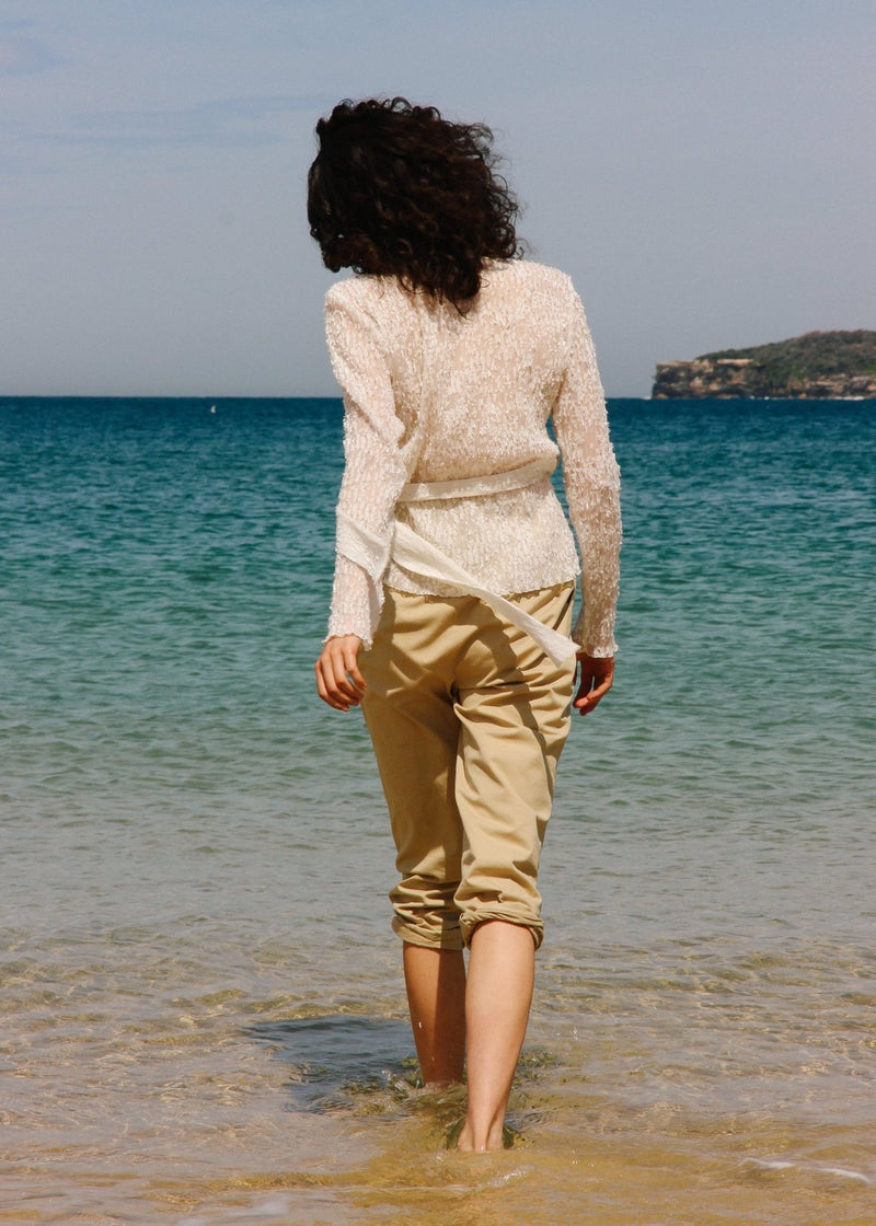 India walking into the ocean wearing the Luela Fil Coupé-Plissé Wrap Top in Vanilla from Laundromat