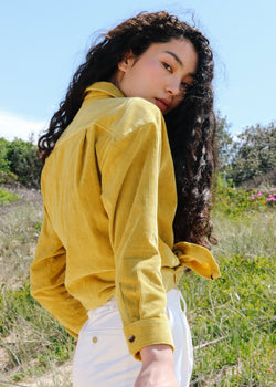 Marlo wears the Luiza Corduroy Shirt in Honeysuckle, tied at the front, from Laundromat