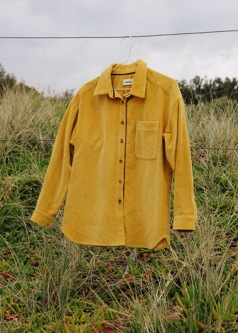 The Luiza Corduroy Shirt in Honeysuckle from Laundromat, hanging on a wire fence in a grassy field