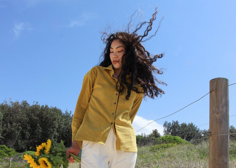 Marlo holding sunflowers, wearing the Luiza Corduroy Shirt in Honeysuckle from Laundromat
