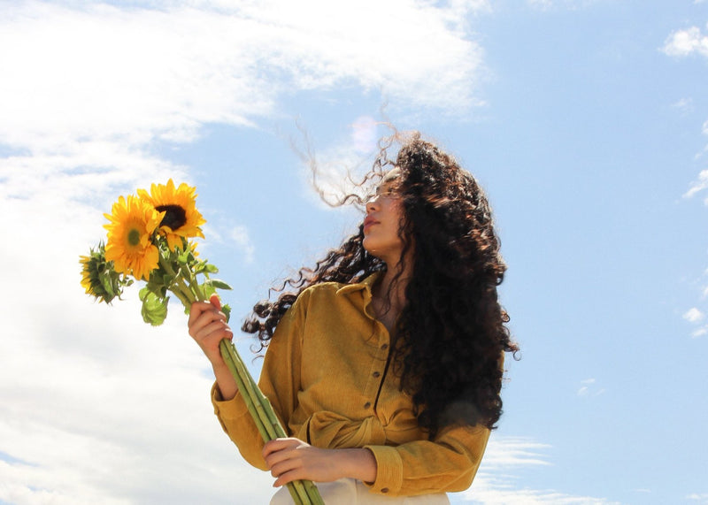Marlo with sunflowers, wearing the Luiza Corduroy Shirt in Honeysuckle from Laundromat