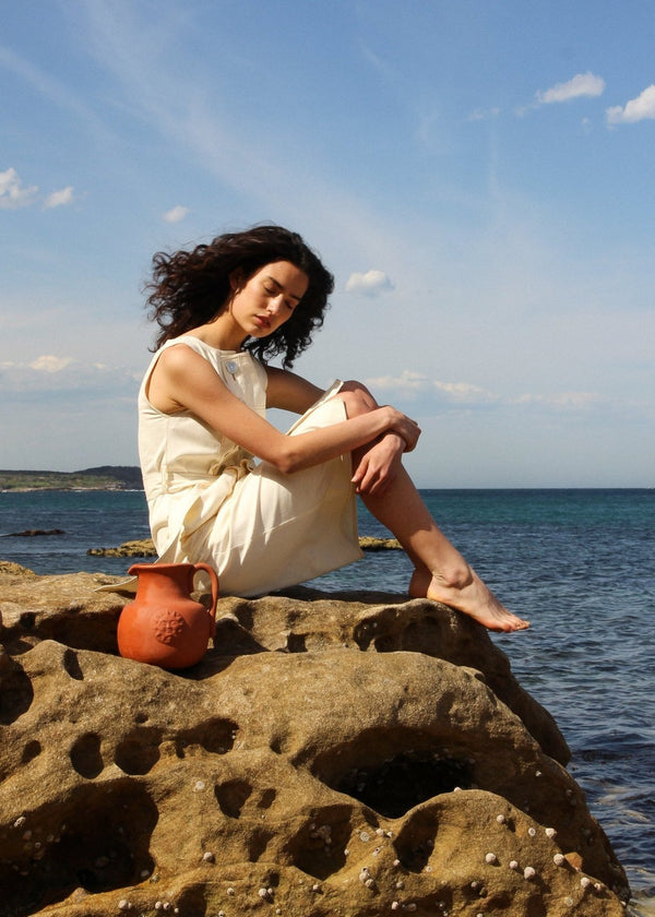 India sitting by the sea wearing the Luna Denim Dress in Double Cream from Laundromat