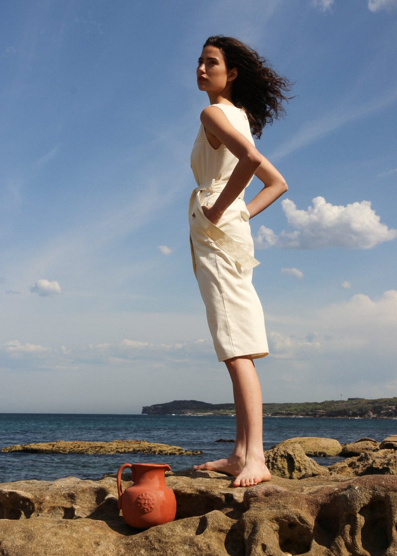India facing the ocean, wearing the Luna Denim Dress in Double Cream from Laundromat
