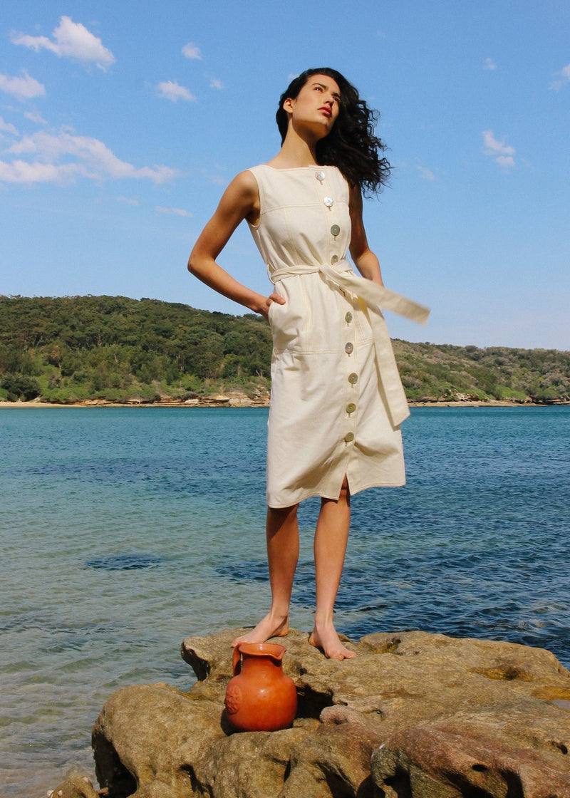 India standing on a rock wearing the Luna Denim Dress in Double Cream from Laundromat