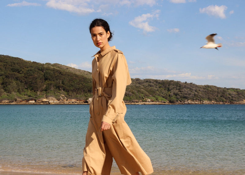 India walking on the beach wearing the Marisol Trench Coat in Biscuit by Laundromat