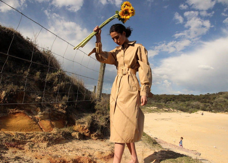 India holding sunflowers wearing the Marisol Trench Coat in Biscuit by the beach, from Laundromat
