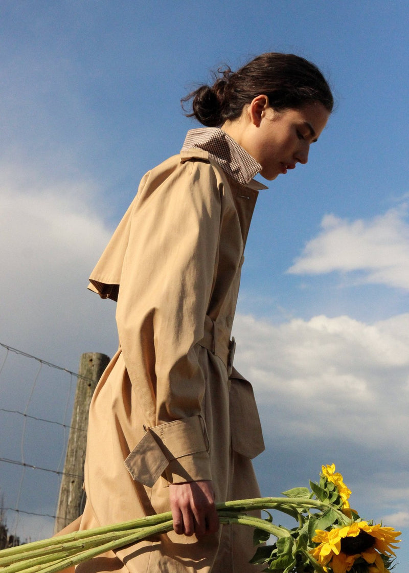 India carrying sunflowers, wearing the Marisol Trench Coat in Biscuit from Laundromat