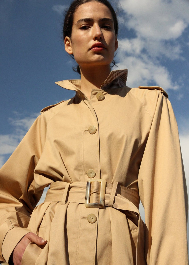 India wears the Marisol Trench Coat in Biscuit with horn buttons from Laundromat