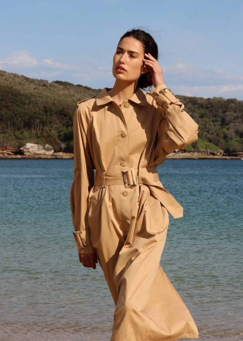India walks by the ocean wearing the Marisol Trench Coat in Biscuit by Laundromat