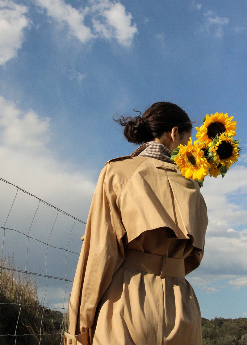India with sunflowers wearing the Marisol Trench Coat in Biscuit from Laundromat