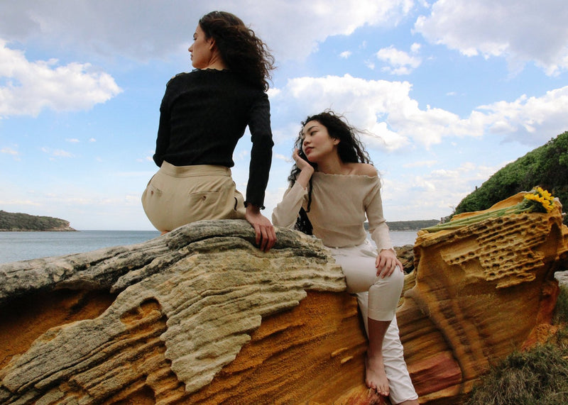 Marlo sitting on a rock with India who wears the Matisse Painter's Trousers in Fallow by Laundromat