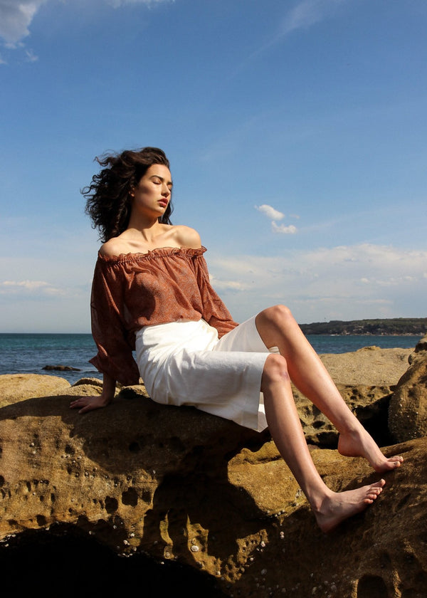 India sitting on a rock wearing the Mireille Blouse in Cinnamon Poppyseed with white wrap dress, both from Laundromat