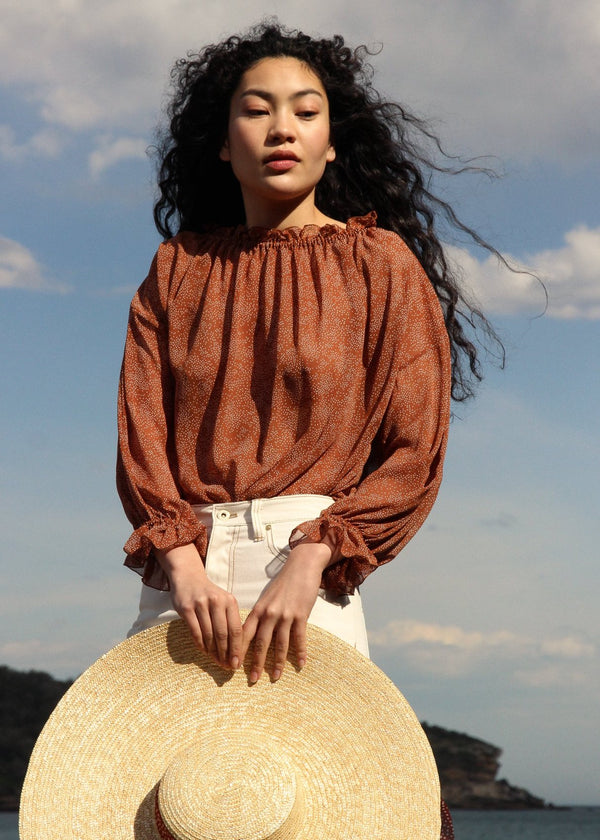 Marlo holding a straw hat, wearing the Mireille Blouse in Cinnamon Poppyseed by Laundromat