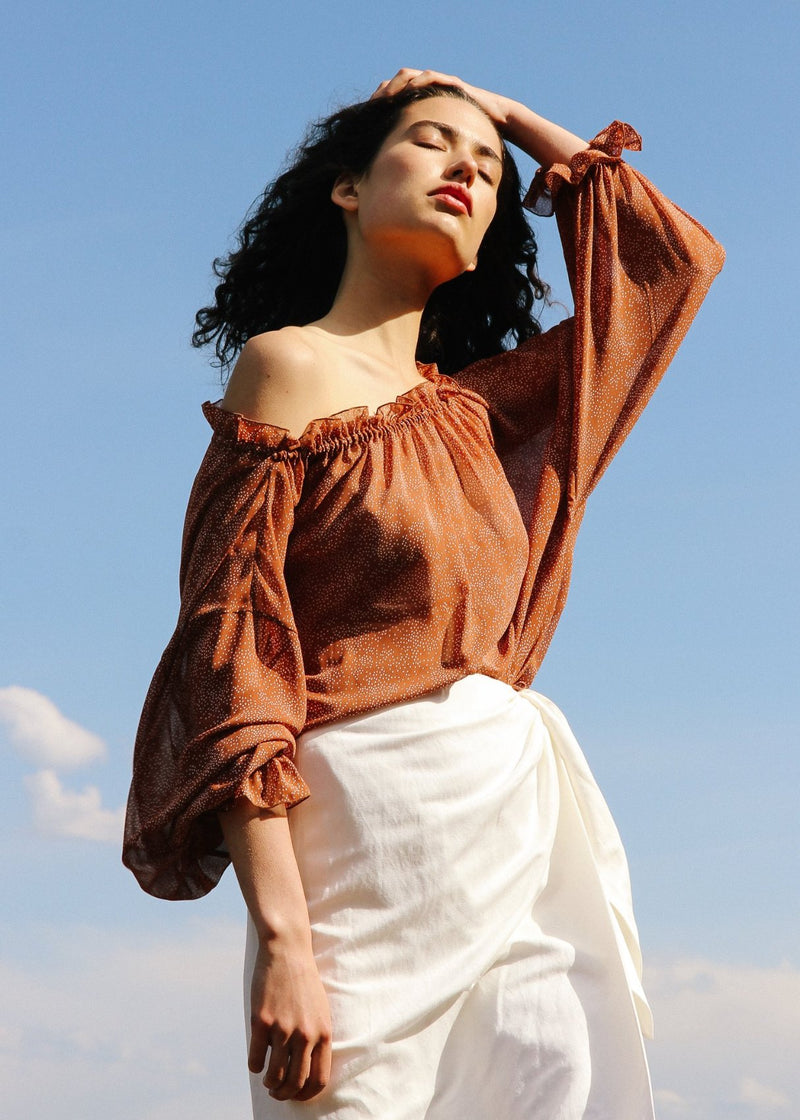India wearing the Mireille Blouse in Cinnamon Poppyseed off-the-shoulder, from Laundromat