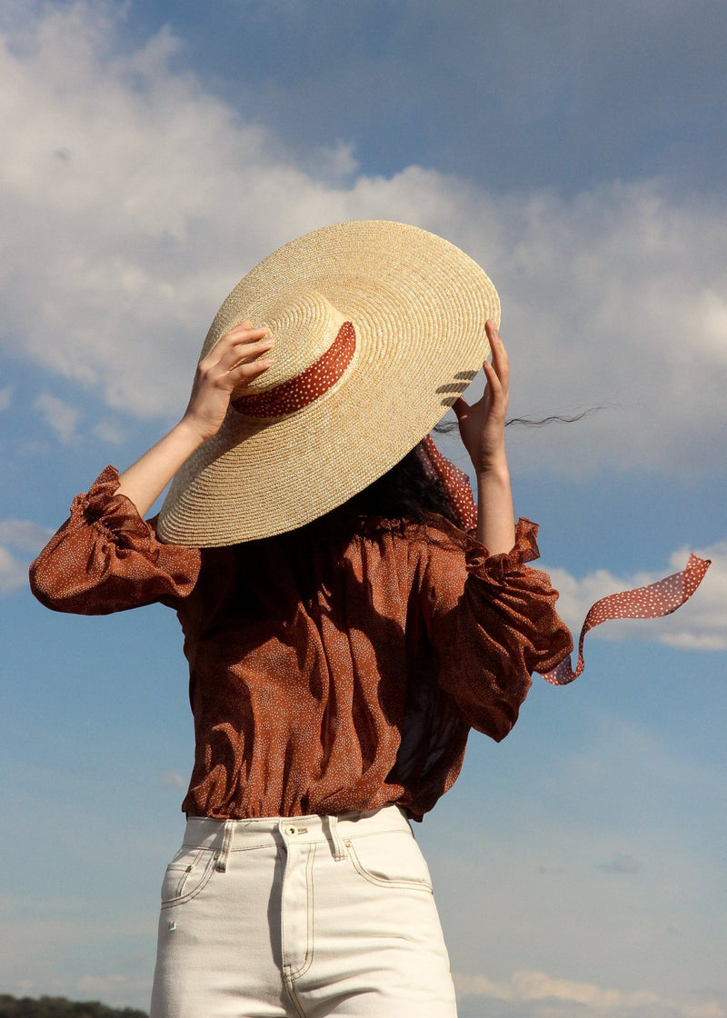 Marlo wearing the Mireille Blouse in Cinnamon Poppyseed and the Clothilde Straw Boater Hat, both by Laundromat