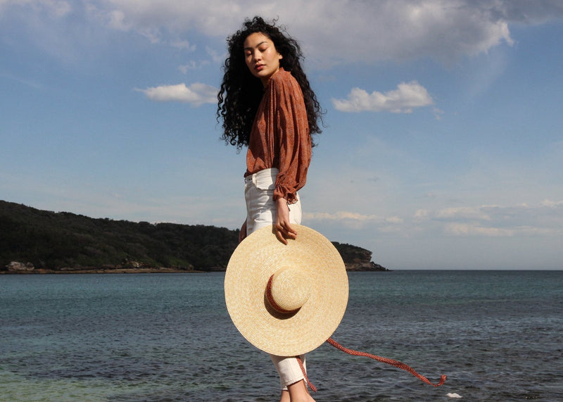 Marlo by the sea wearing the Mireille Blouse in Cinnamon Poppyseed, carrying a straw hat, both from Laundromat