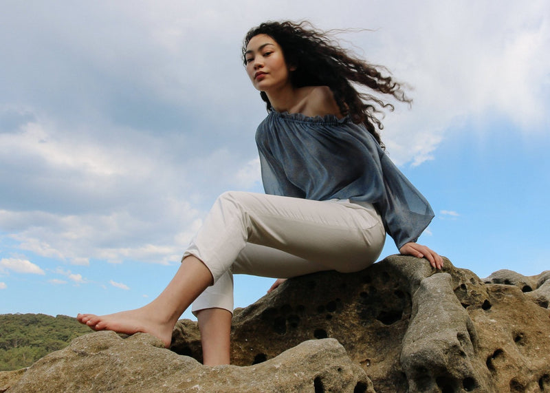 Marlo sitting on a rock wearing the Mireille Blouse in Cornflower Poppyseed with cream trousers, both from Laundromat