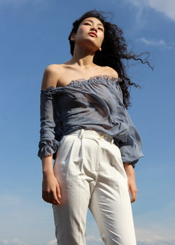 Marlo wears the Mireille Blouse in Cornflower Poppyseed off-the-shoulder with white trousers, both from Laundromat
