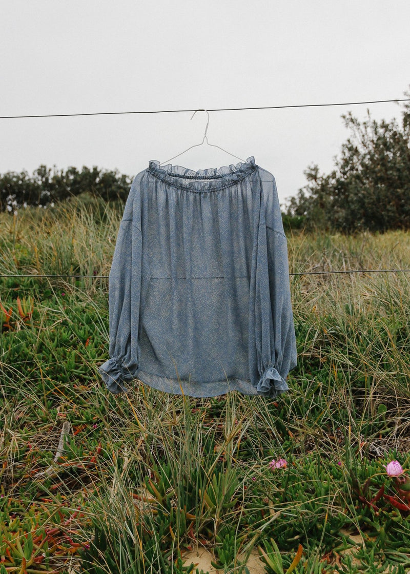 The Mireille Blouse in Cornflower Poppyseed hanging on a fence in a grassy field