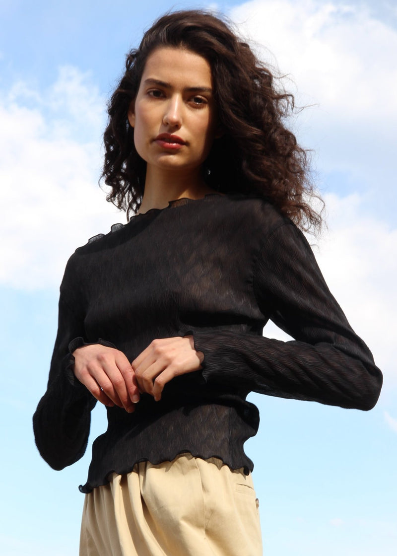 India wears the Oriana Wave Plissé Top in Ebony from Laundromat