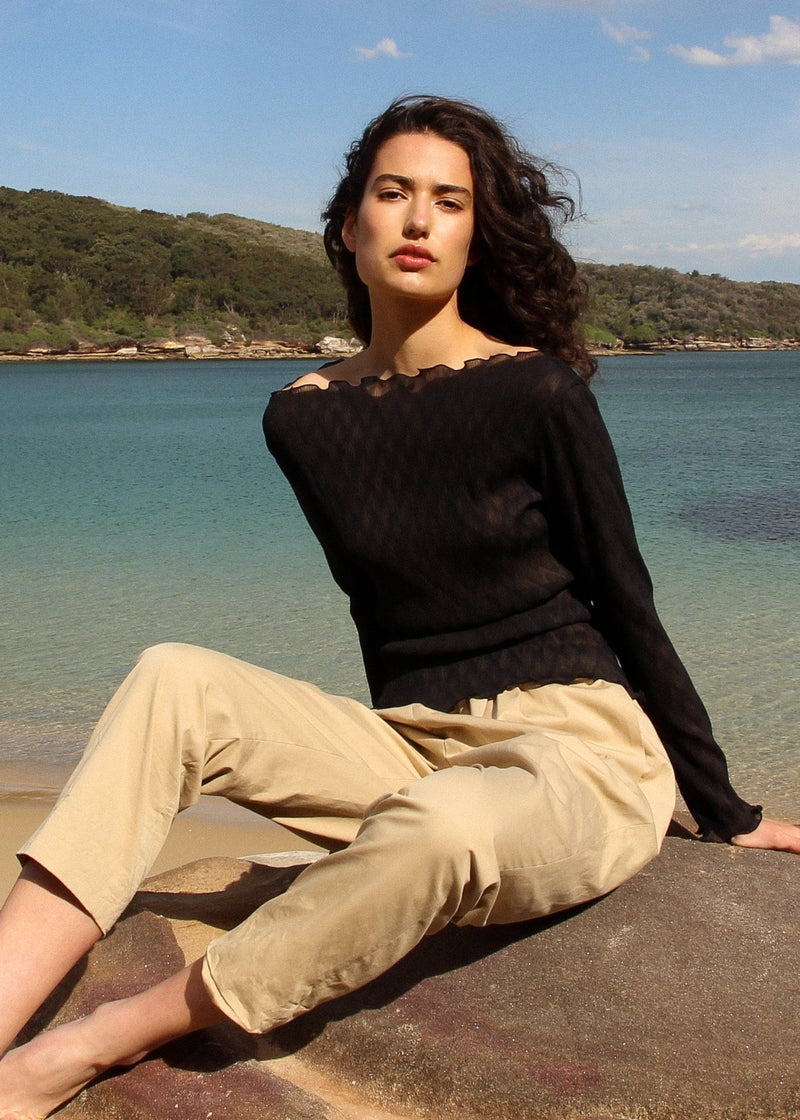 India sitting by the ocean wearing the Oriana Wave Plissé Top in Ebony from Laundromat