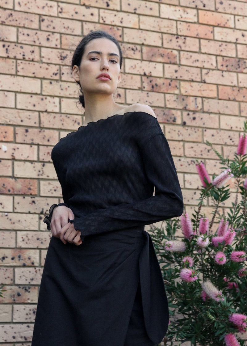 India wearing the Oriana Wave Plissé Top in Ebony with the Anais Wrap Skirt, both by Laundromat
