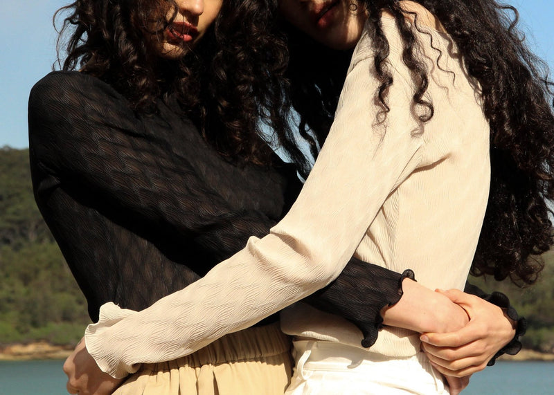 Detail of the Oriana Wave Plissé Top worn by India and Marlo, both from Laundromat