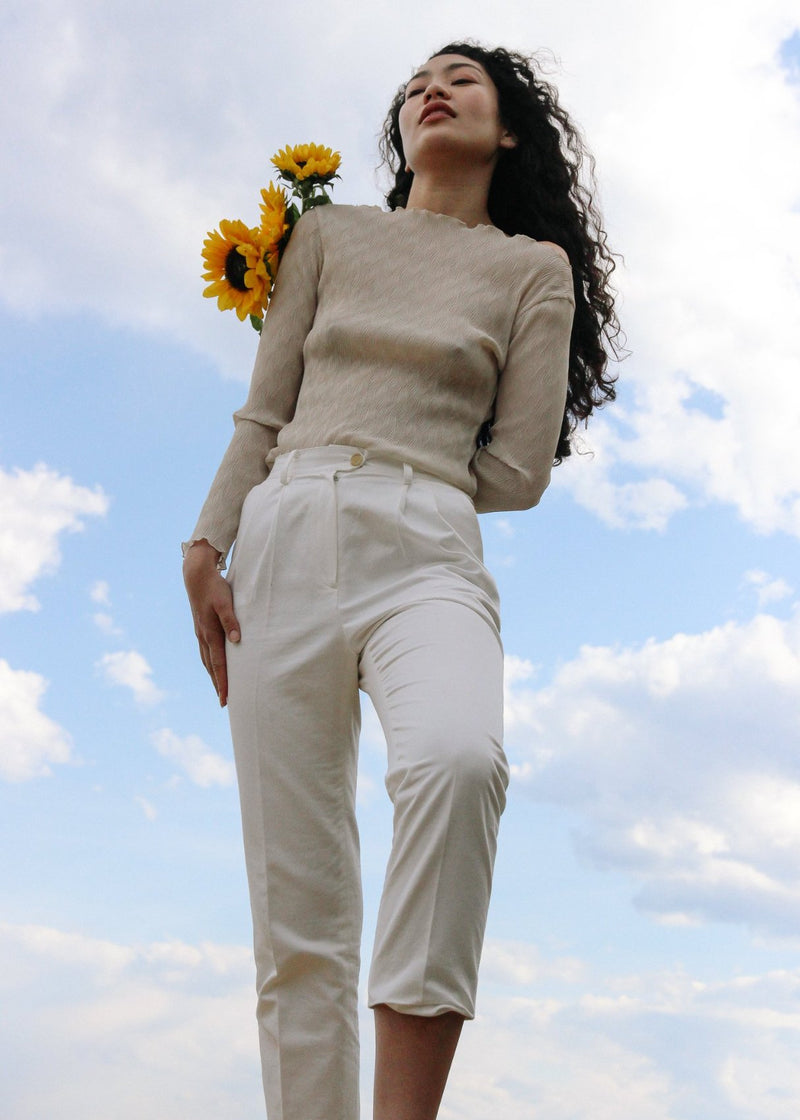Marlo with sunflowers wearing the Oriana Wave Plissé Top in Oyster Shell with the Elaine Pleat Trousers, both by Laundromat