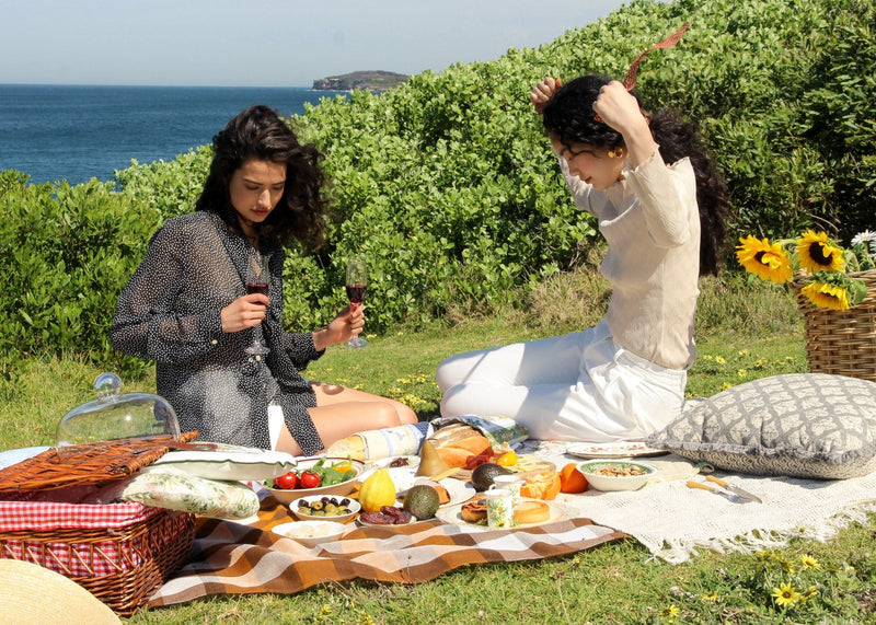 India picnicking with Marlo who wears the Oriana Wave Plissé Top in Oyster Shell from Laundromat