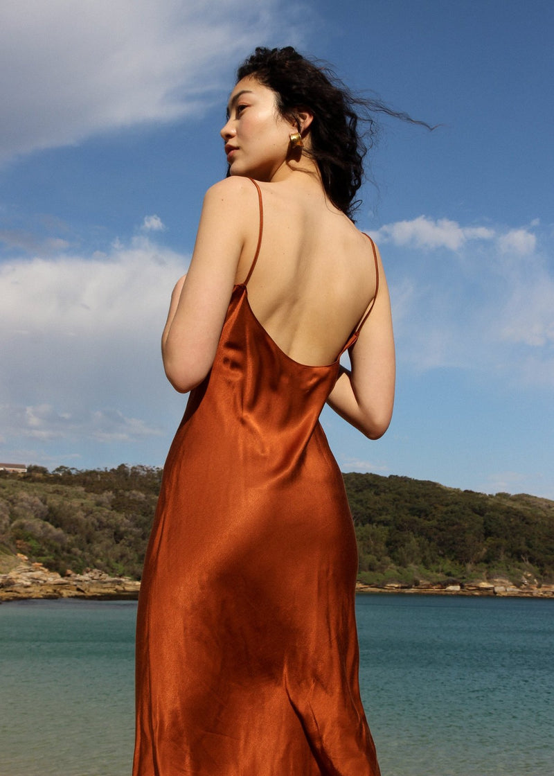 Marlo facing the ocean wearing the Salma Slip Dress in Sienna from Laundromat