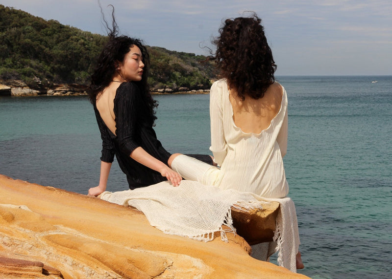 Marlo and India sitting on a rock edge, both wearing the Severina Plissé Dress from Laundromat