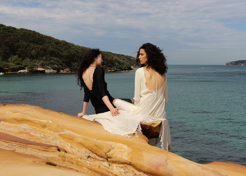 Marlo and India looking out to sea, both wearing the Severina Plissé Dress from Laundromat