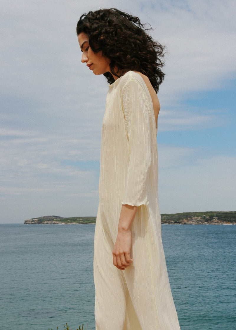 India by the sea wearing the Severina Plissé Dress in Pearl from Laundromat