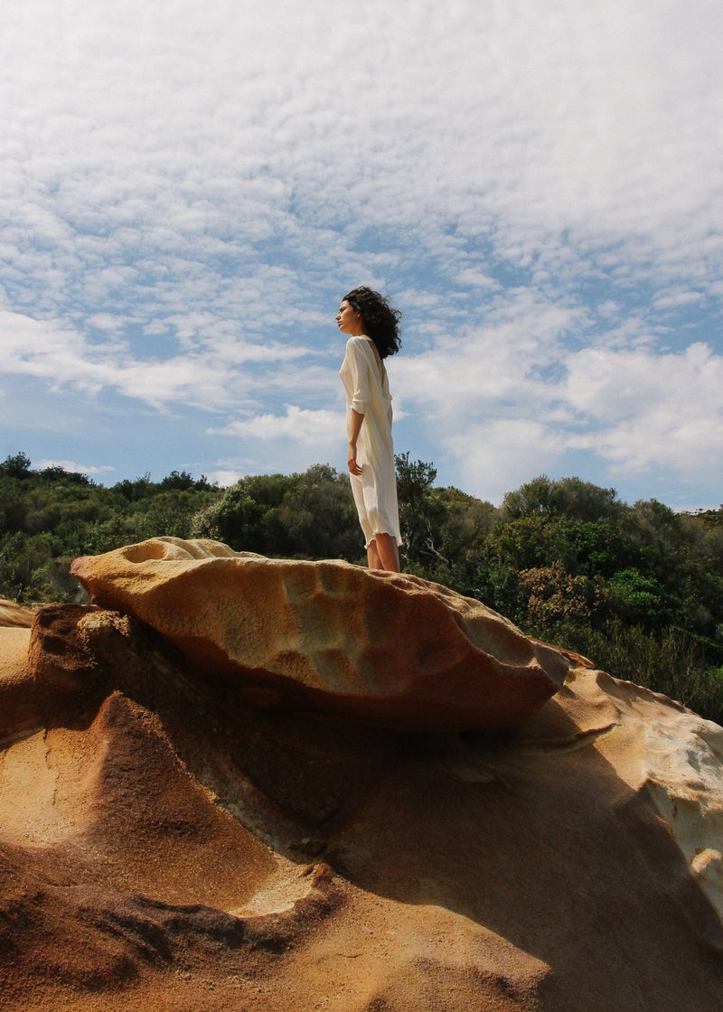 India standing on a rock in the Severina Plissé Dress in Pearl from Laundromat