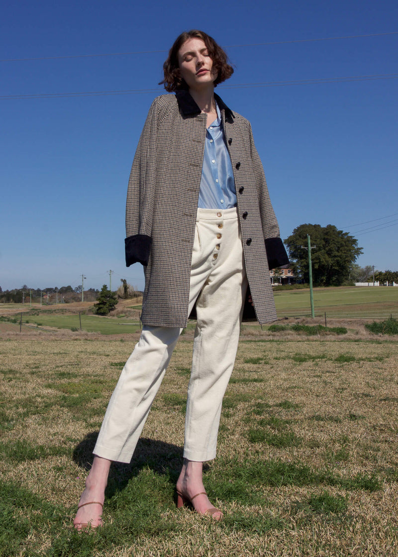 Olivia wears the Rumi Corduroy Button-up Trousers and wool coat both from Laundromat