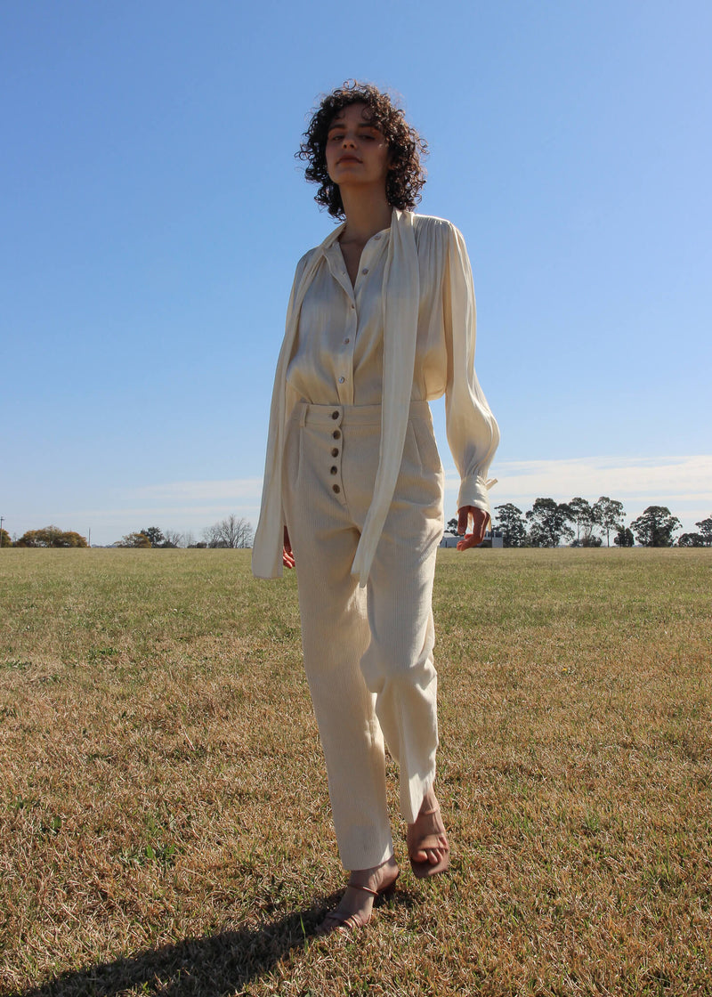 Maya wearing the Rumi Corduroy Button-up Trousers and white blouse