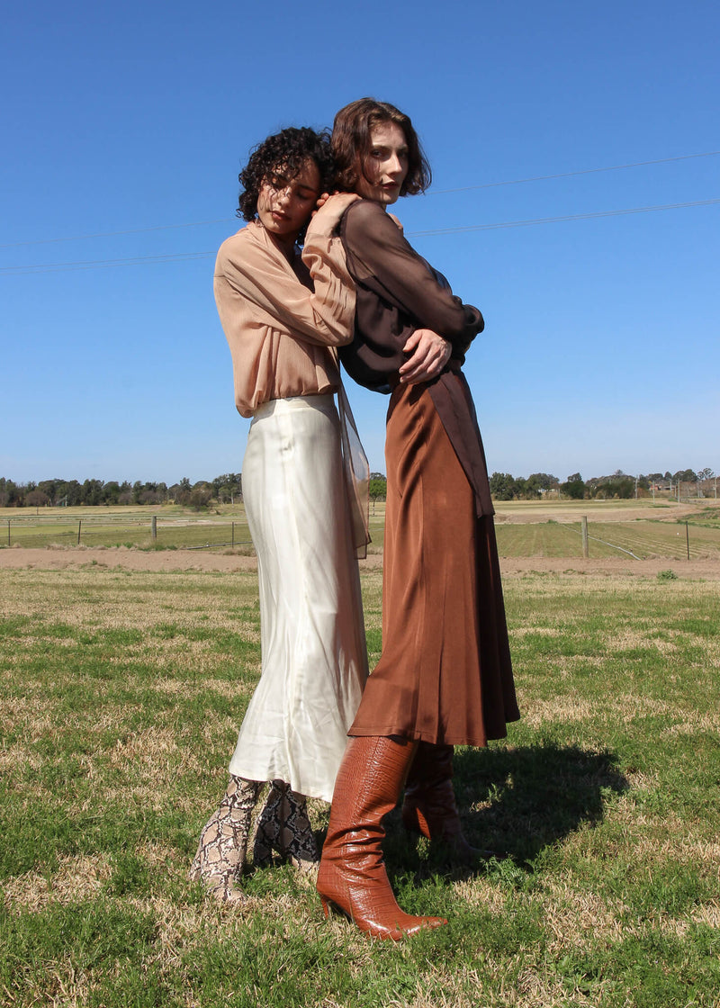 Maya and Olivia both wear the Yasmin Bias Slip Skirt from Laundromat