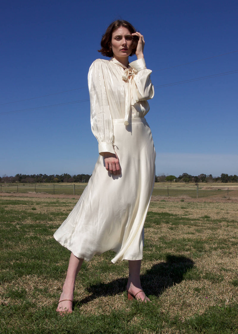 Olivia wears the Yasmin Bias Slip Skirt and blouse, both from Laundromat