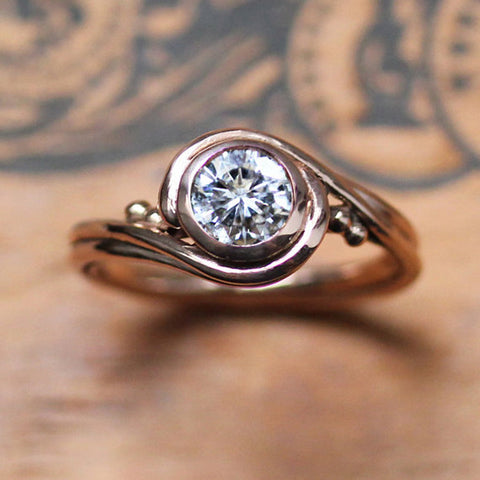 Rose gold ring with swirling features and faceted moissanite gemstone.