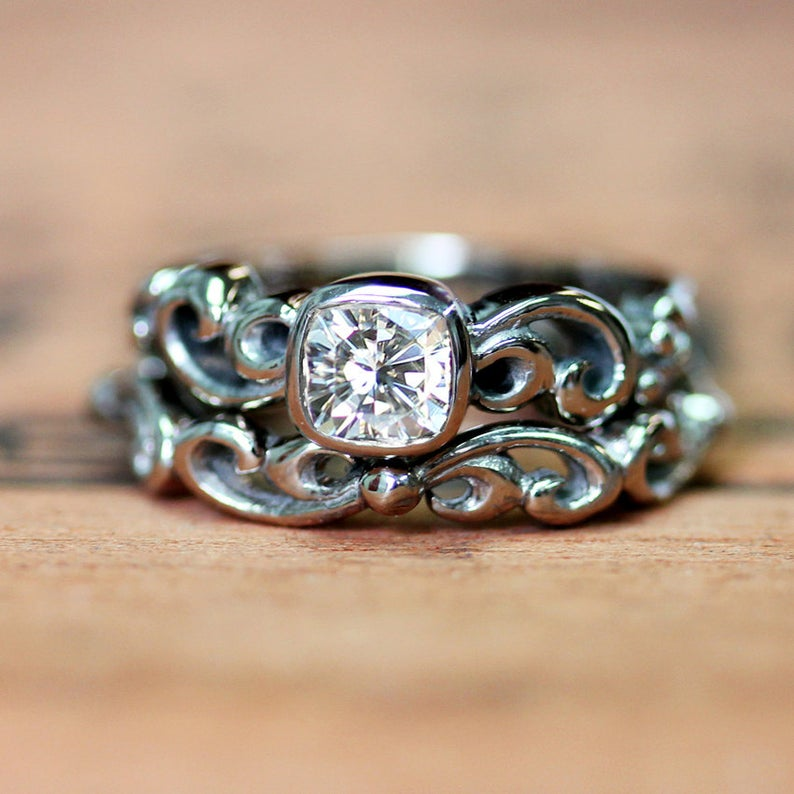 White gold bridal ring sent with infinity symbol details and moissanite gemstone.