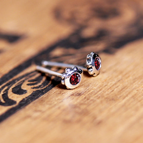 Stud earrings with bead details around the outside and birthstones.