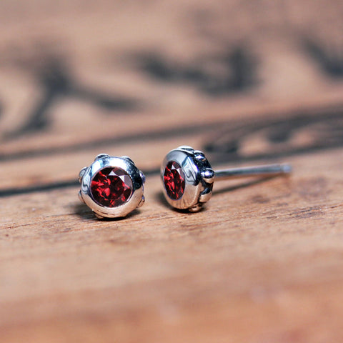 Sterling silver studs with beading and garnet or white topaz stones.