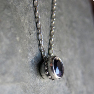 Side view of amethyst bezel necklace in sterling silver with beaded detail on the sides