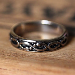 Men's white gold wedding band with infinity detailing and black enamel.