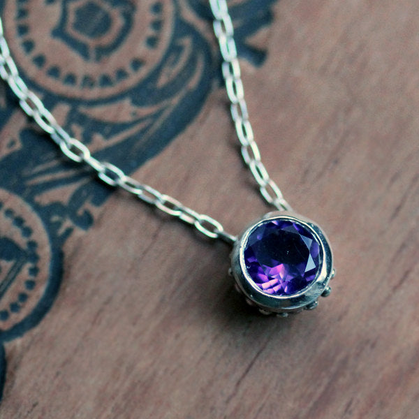 Round amethyst bezel necklace in sterling silver on wood background