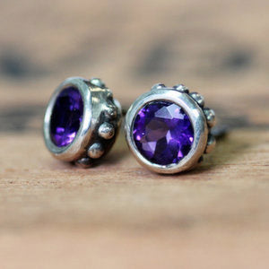 Sterling silver studs with purple amethyst gemstones.