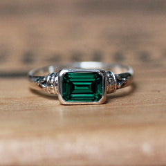 green emerald ring that is emerald cut and bezel set into a sterling silver vintage style setting