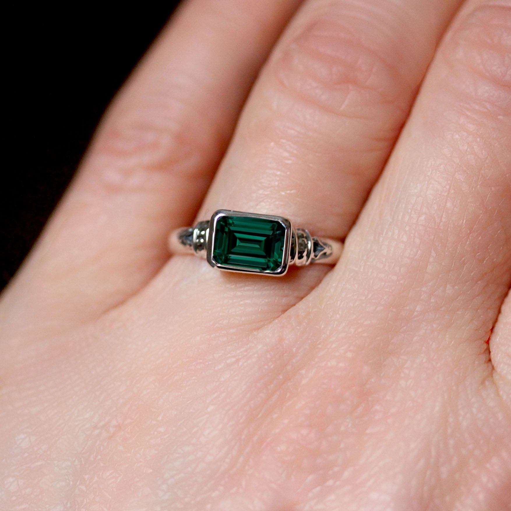 Green emerald cut emerald ring on the hand