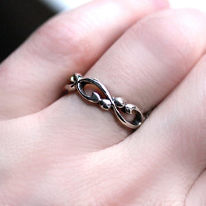Silver infinity filigree band being worn on a woman's hand